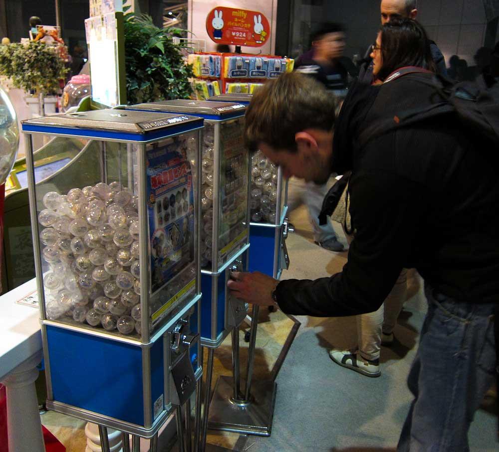 homem branco inserindo moedas nas máquinas de gachapon, que inspiraram muitos jogos pay to win