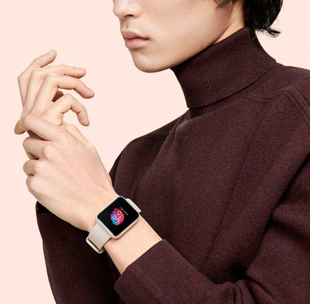 mulher com casaco de gola alta usando um redmi watch no pulso