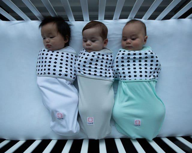 3 bebês em um berço usando as faixas de respiração da Nanit