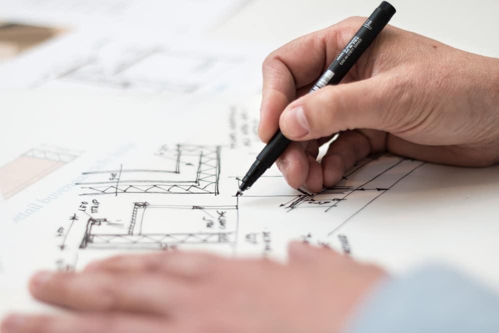 desenho de estrutura em mesa, com homem segurando uma caneta e desenhando nela