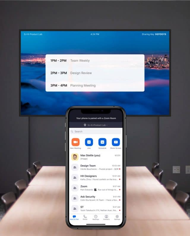 sala de reuniões com celular e tela exibindo app aberto